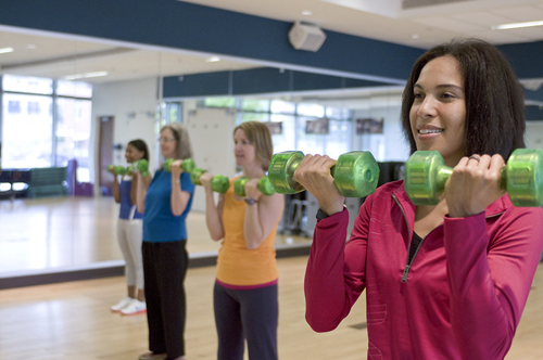 lady at the gym exercising with dumbbells