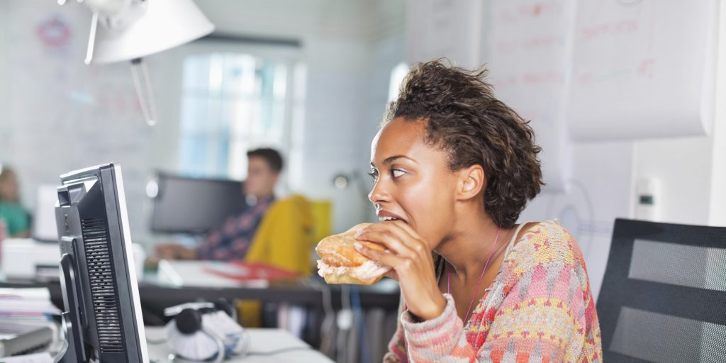 workplace nutrition - young lady taking a big bite
